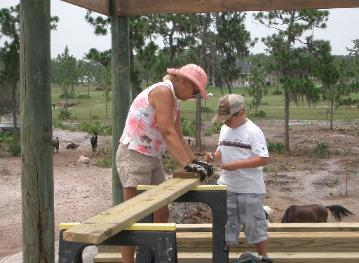 Winnie and our grandson Cody marking and cutting rafters.